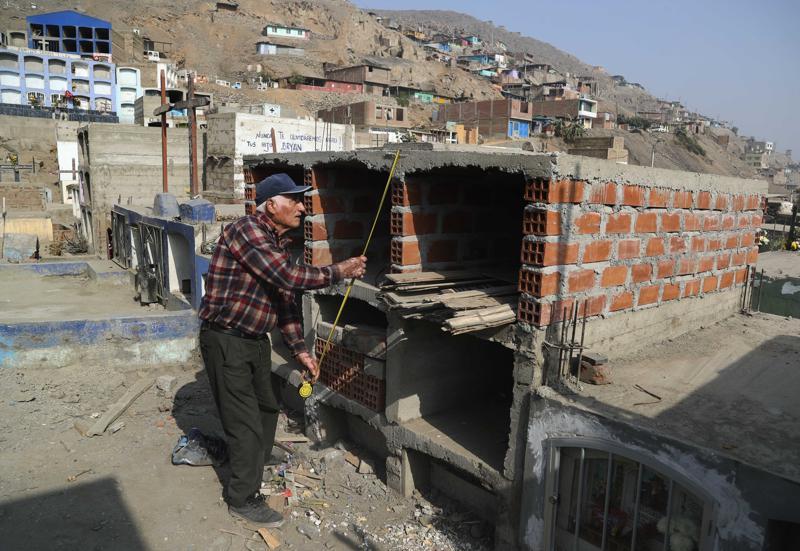 Thương gia nghỉ hưu Victor Coba đo đạc những ngôi mộ mà ông đang xây cho gia đình mình tại nghĩa trang San Lazaro ở ngoại ô Lima, Peru.