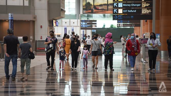Những dân đeo khẩu trang bảo hộ đi bộ tại nhà ga số 3 ở sân bay Changi, Singapore.