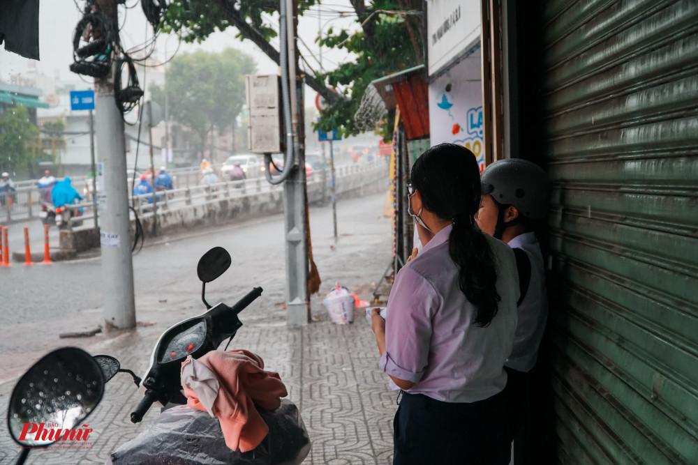 Các máy hiên khu vực gần trường học được các em tận dụng để núp mưa