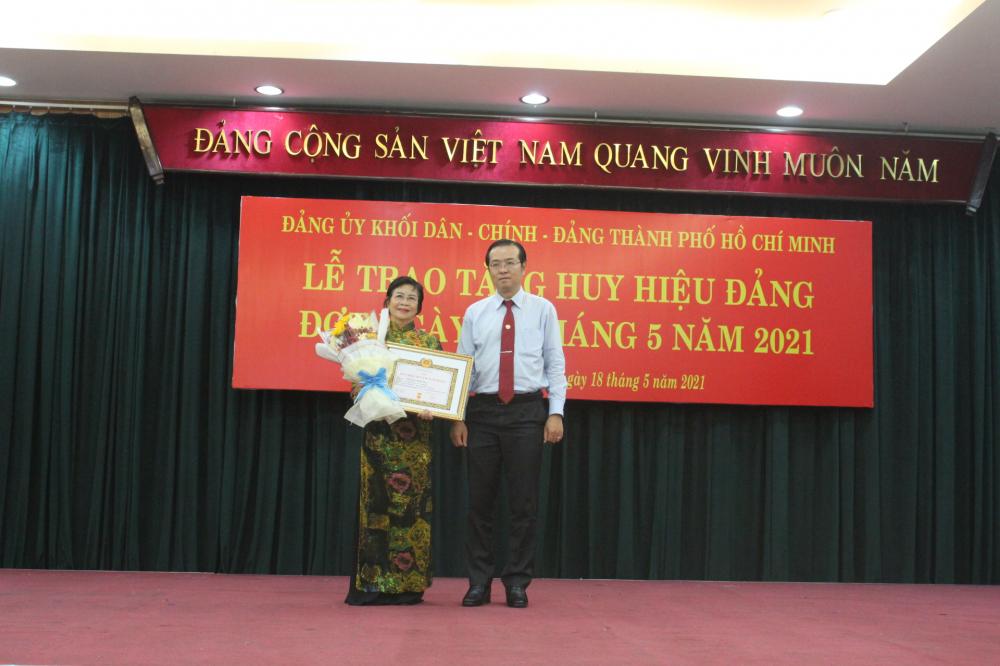 Phó trưởng Ban Thường trực Ban Tuyên giáo Thành ủy TPHCM Lê Văn Minh trao huy hiệu 50 năm tuổi Đảng cho nghệ sĩ Tô Nguyệt Nga.