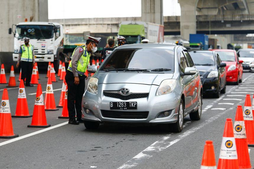 Cảnh sát kiểm tra xe hơi tại một trạm kiểm soát ở Cikarang, ngoại ô Jakarta, ngày 17/5 - Ảnh: Reuters