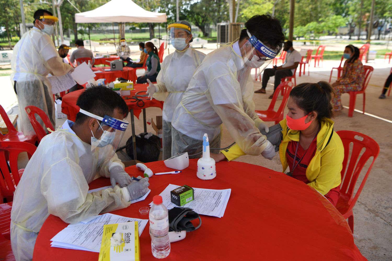 Nhân viên y tế đang kiểm tra tình trạng sức khỏe của công nhân nhập cư ở Cambodia - Ảnh: Tang Chhin Sothy/Getty Images