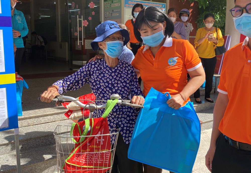 Bà Trần Thị Phương Hoa hỏi han, hỗ trợ một cụ già đạp xe đến nhận quà