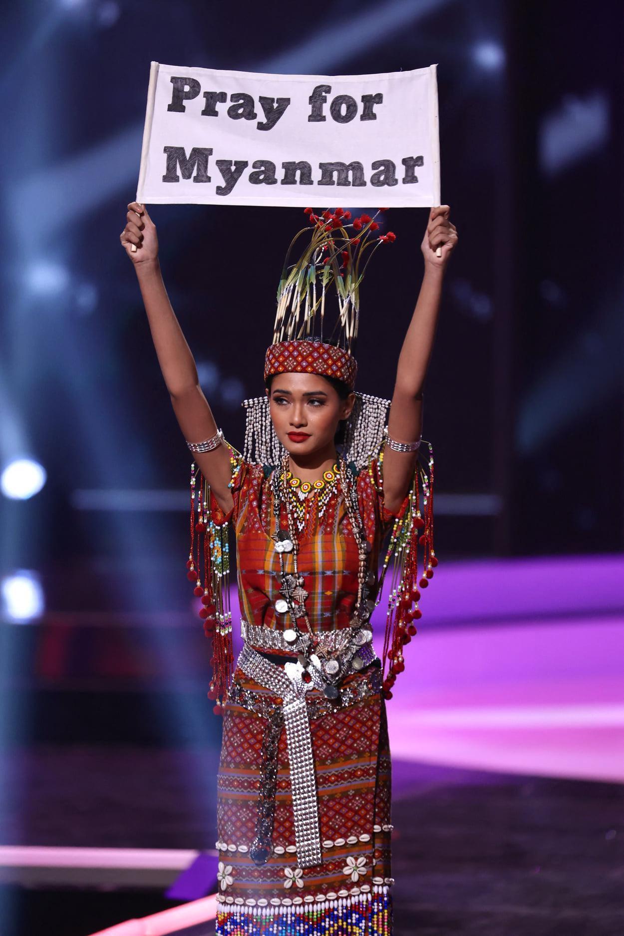 Hoa hậu Hoàn vũ Myanmar giơ tấm bảng Cầu nguyện cho Myanmar trong phần thi Trang phục dân tộc tại Miss Universe 2020