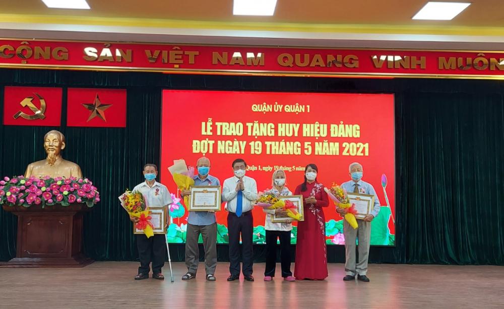 Chủ tịch UBND TPHCM Nguyễn Thành Phong và Bí thư Quận ủy quận 1 Trần Kim Yến trao huy hiệu 60 năm tuổi Đảng.