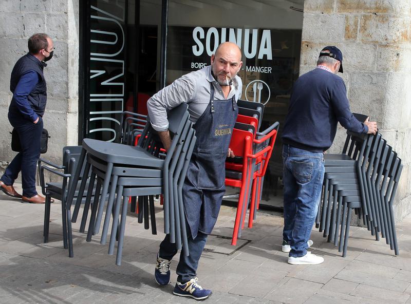 Nhân viên một nhà hàng ở Bayonne, Tây Nam nước Pháp, xếp ghế trên vỉa hè phố để chuẩn bị đón khách vào ngày 19/5 - Ảnh: AP