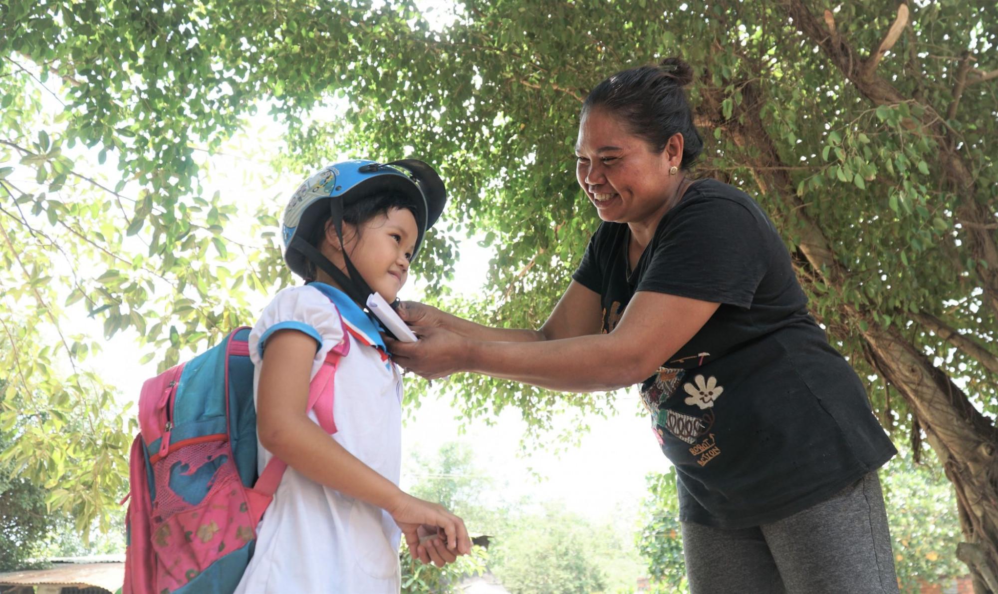 Già làng Keo Onl hướng dẫn trẻ đội mũ bảo hiẻm đúng cách - Ảnh: Hồng Thắm