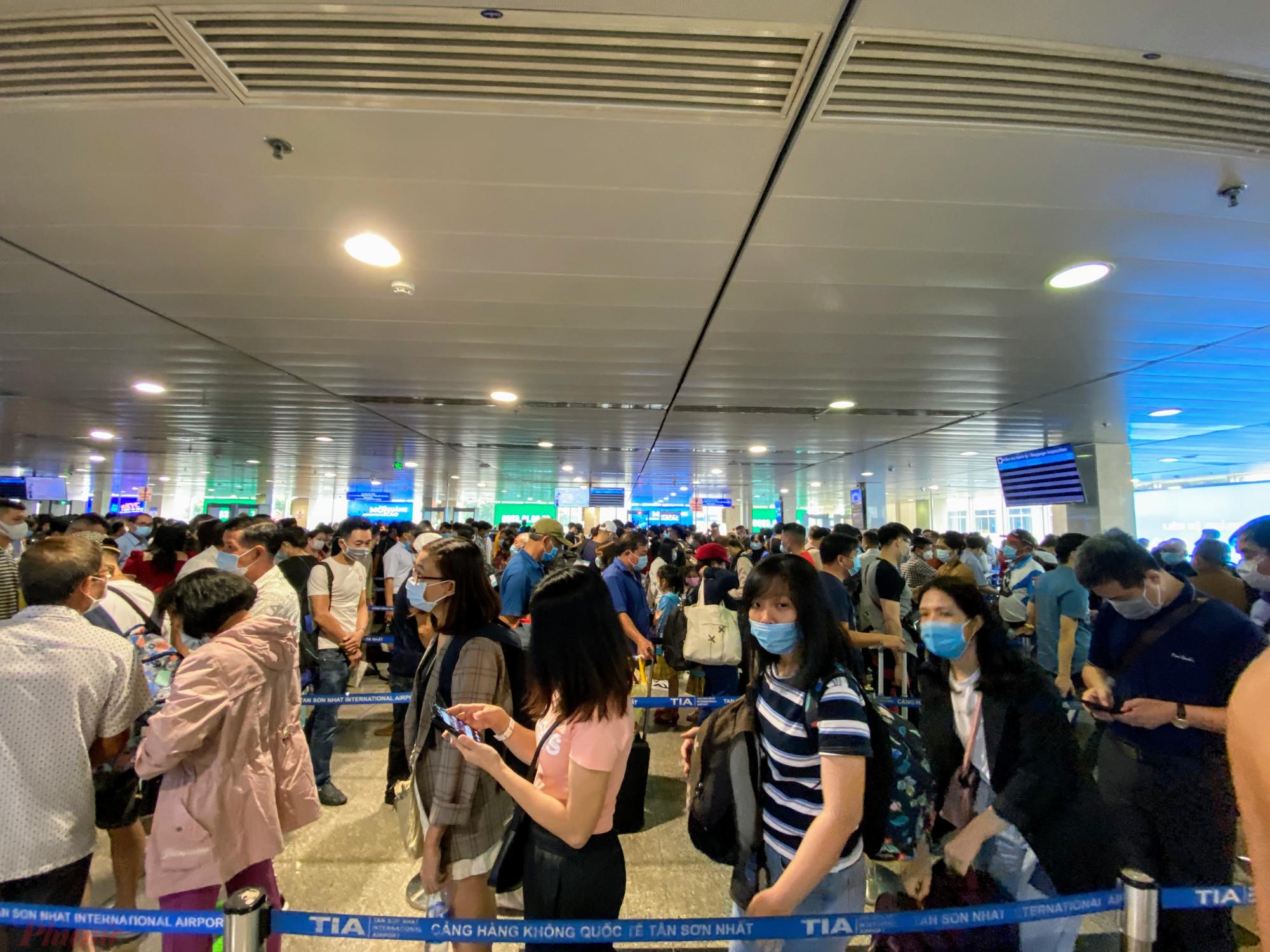 Khách hàng rồng rắn xếp hàng chờ soi chiếu an ninh tại sân bay Tân Sơn Nhất. Ảnh: Quốc Thái