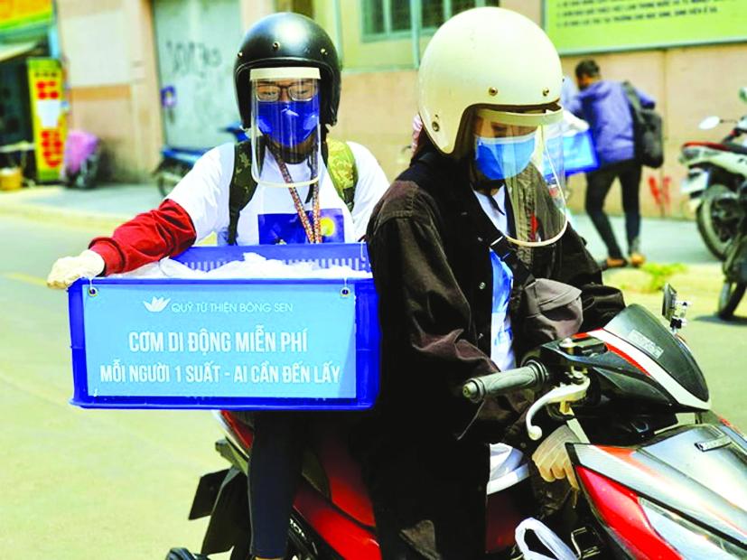 Tình nguyện viên quán Nụ Cười 6 khi đi tặng cơm đều được trang bị bảo hộ để phòng tránh lây nhiễm - ẢNH: NGUYỄN TẬP