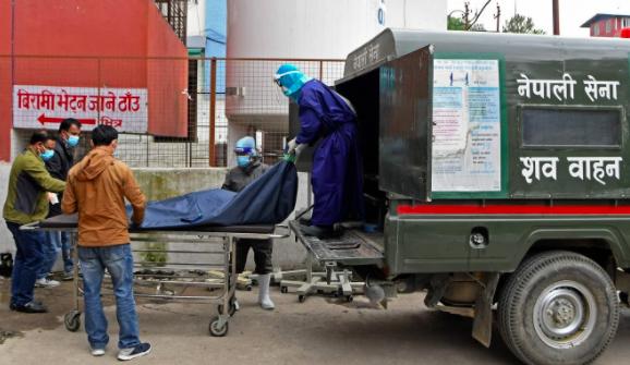 Các nhân viên quân đội và nhân viên y tế Nepal chuyển thi thể của một bệnh nhân tử vong vì Covid-19 vào xe cứu thương bên ngoài nhà xác ở Kathmandu. Ảnh: AFP