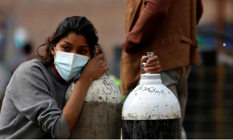 Một phụ nữ ở Kathmandu, Nepal, cầm bình oxy rất cần thiết cho một bệnh nhân Covid-19 sau khi đổ đầy bình tại một nhà máy. Ảnh: Reuters
