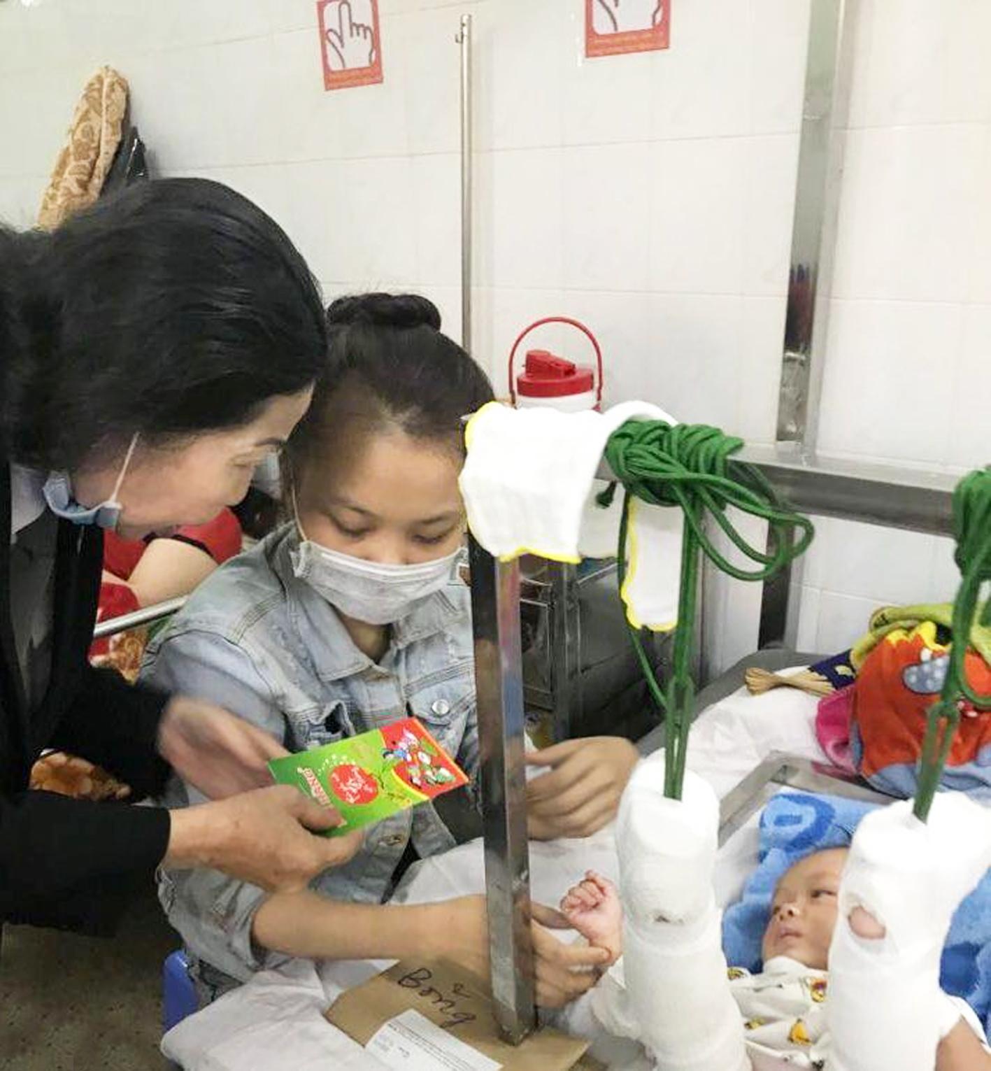 Luật sư Trần Thị Ngọc Nữ cùng Hội LHPN TP.HCM vào bệnh viện thăm em bé bốn tháng tuổi bị cha bạo hành