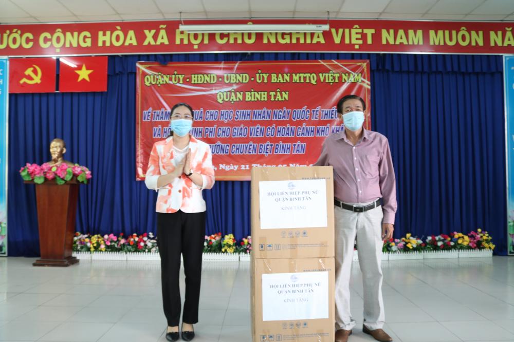 Chị Huỳnh Đặng Hà Tuyên - Chủ tịch Hội LHPN quận Bình Tân - trao tặng khẩu trang y tế cho đại diện trường.