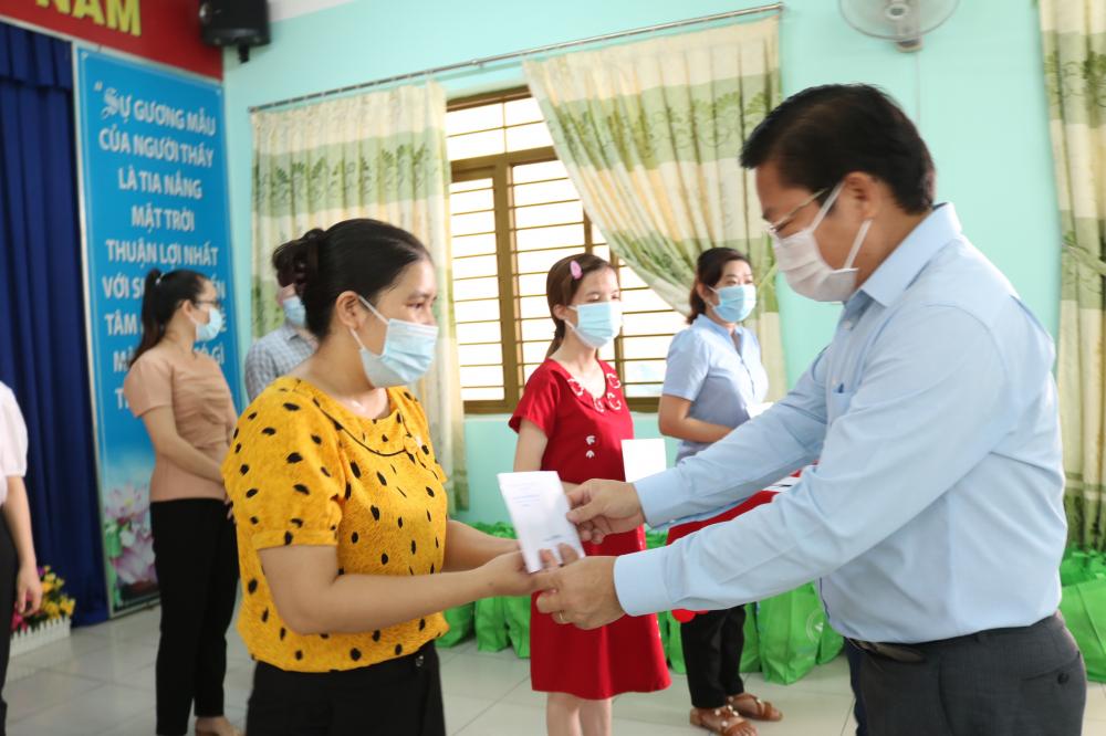 Ông Lê Văn Thinh - Bí thư Quận ủy, Chủ tịch HĐND quận Bình Tân - trao tiền hỗ trợ cho thầy cô giáo và nhân viên nhà trường.