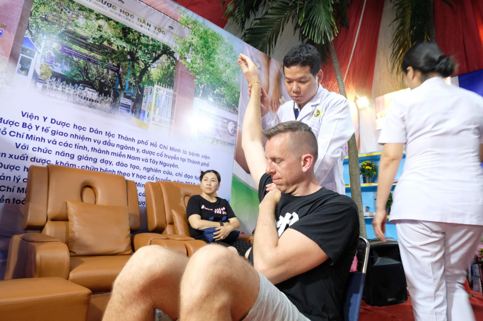 Y bác sĩ Viện Y Dược học dân tộc TPHCM tập vật lý trị liệu cho du khách nước ngoài tại một hội chợ du lịch quốc tế năm 2019 - Ảnh: Chế Trung.