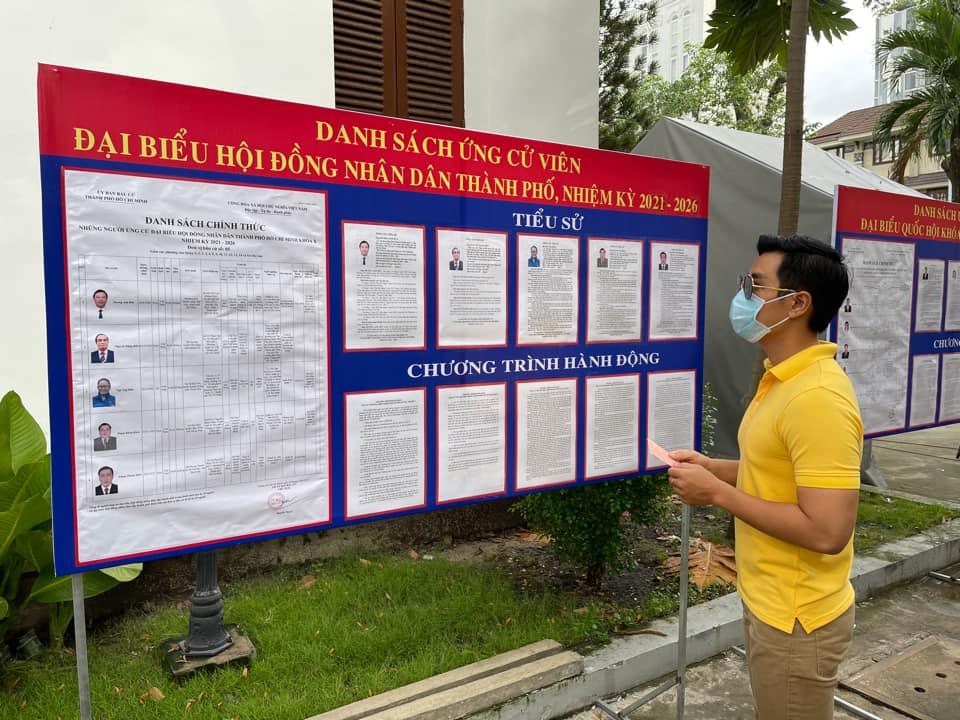 Anh xem lại danh sách ứng cử viên và chương trình hành động của họ trước khi bỏ phiếu.