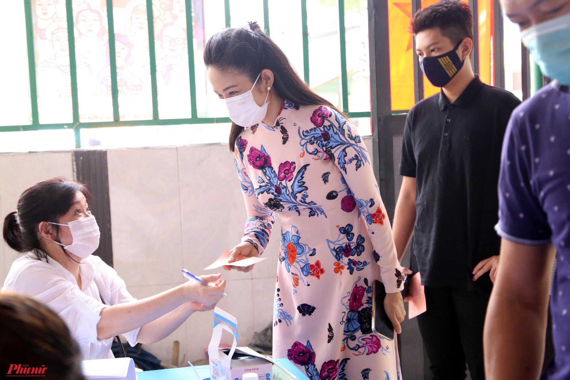 Nữ nghệ sĩ được cán bộ địa phương kiểm tra thân nhiệt, kiểm tra các thông tin cần thiết trước khi bỏ phiếu bầu cử.