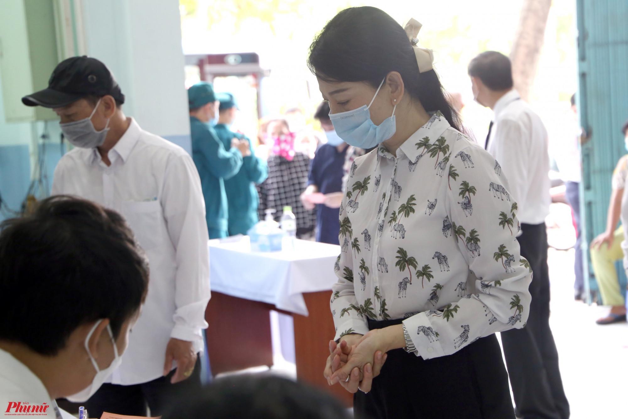 Mỹ Uyên thực hiện các thao tác khai báo y tế, đo thân nhiệt và được kiểm tra lại thông tin trước khi bỏ phiếu.