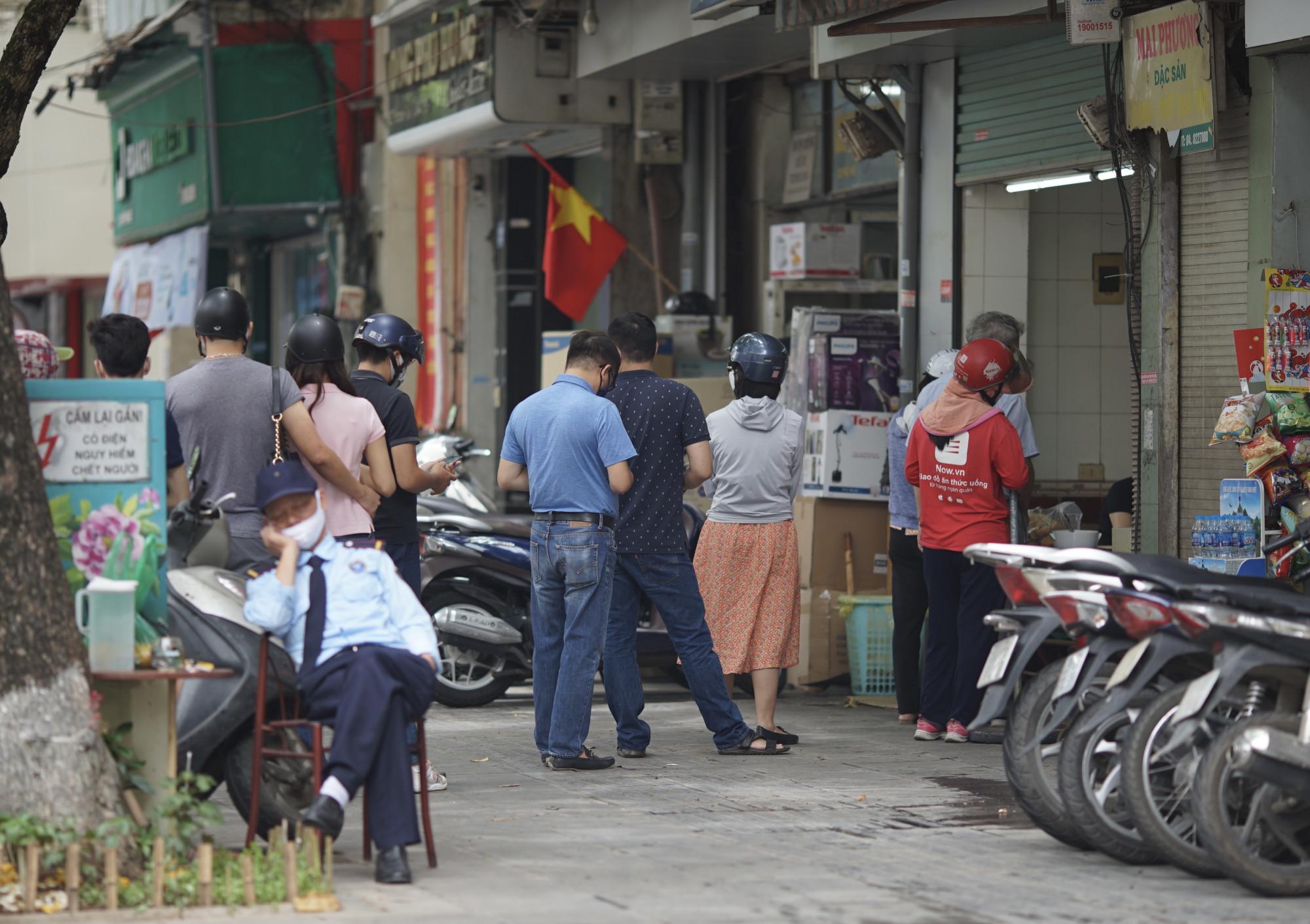 Trong khi hầu hết quán ăn vắng khách thì vẫn còn những quán bán đồ ăn nhanh như bánh mỳ, xôi lại nhiều người đến mua về.