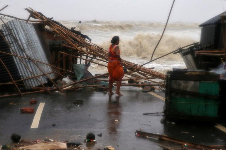 Một người phụ nữ đứng cạnh quầy hàng của cô, bị hư hại do gió lớn tại bờ biển ở Bichitrapur thuộc quận Balasore, phía đông bang Odisha