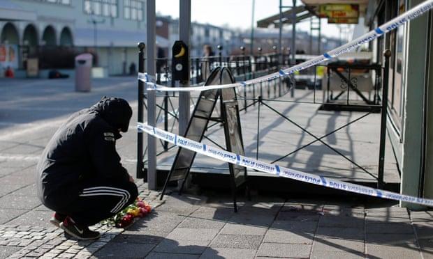 Một người đàn ông đang cắm hoa tại hiện trường một vụ xả súng chết người ở Gothenburg, Thụy Điển, năm 2015.