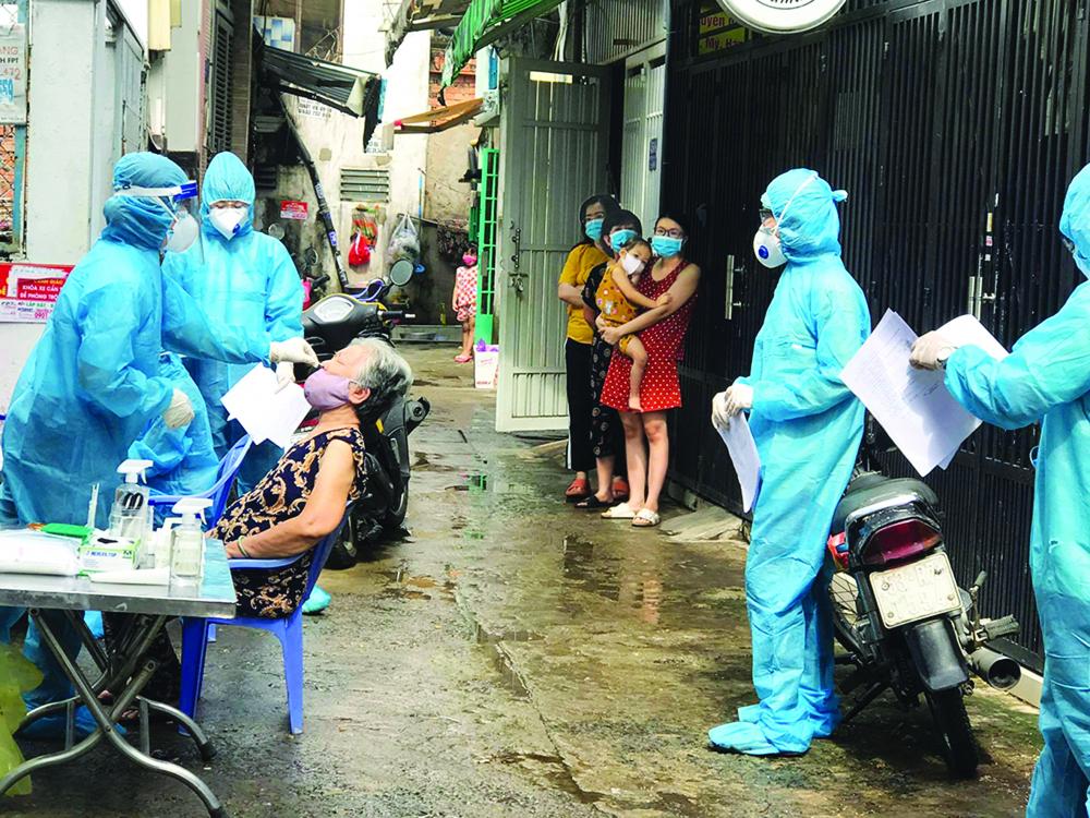 Lấy mẫu xét nghiệm vi-rút SARS-CoV-2 vớ i người dân trong hẻm 1358/30 Quang Trung, P.14, Q.Gò Vấp, TP.HCM Ả NH: PHẠM AN