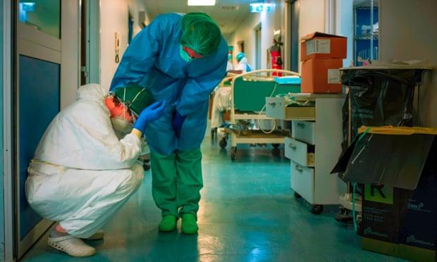 Một y tá ở Ý an ủi một đồng nghiệp khi thay ca trong đợt Covid đầu tiên tại bệnh viện Cremona. Đại dịch đã đẩy nhanh số lượng y tá rời bỏ nghề do kiệt sức và căng thẳng. Ảnh: Paolo Miranda / AFP / Getty