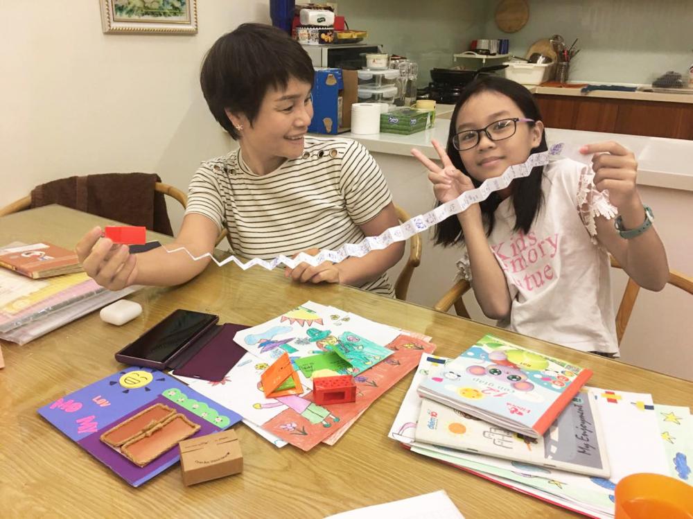 Chị Thu Hà bất ngờ với quà tặng con gái út thiết kế - hộp nến bằng giấy bên trong chứa quyển sổ lò xo đầy tranh vẽ và lời yêu thương