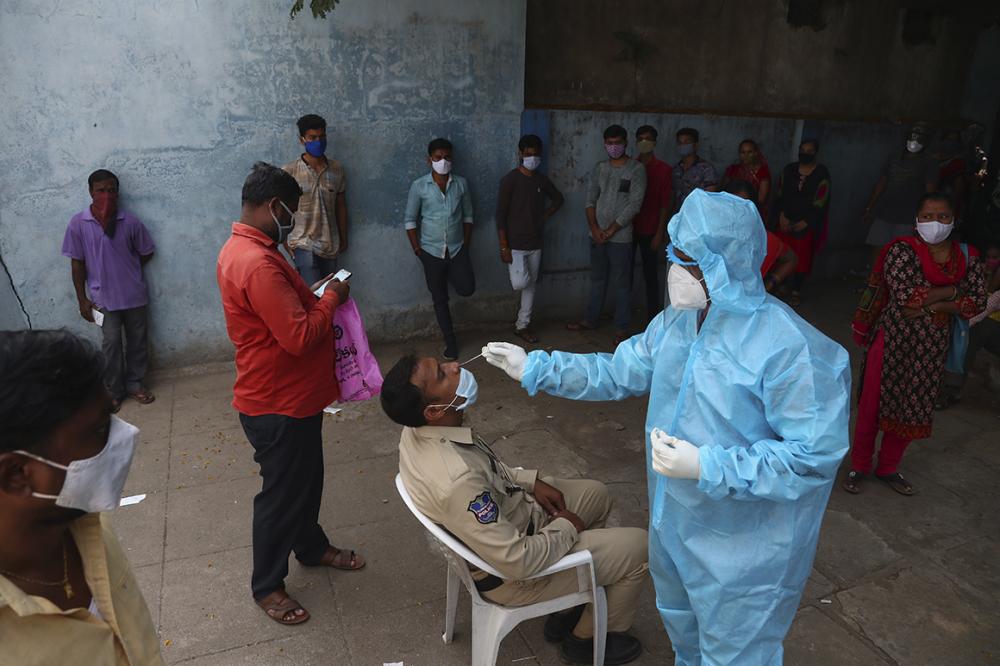 Nhân viên y tế lấy mẫu xét nghiệm COVID-19 tại một bệnh viện công ở Hyderabad, Ấn Độ - Ảnh: AP