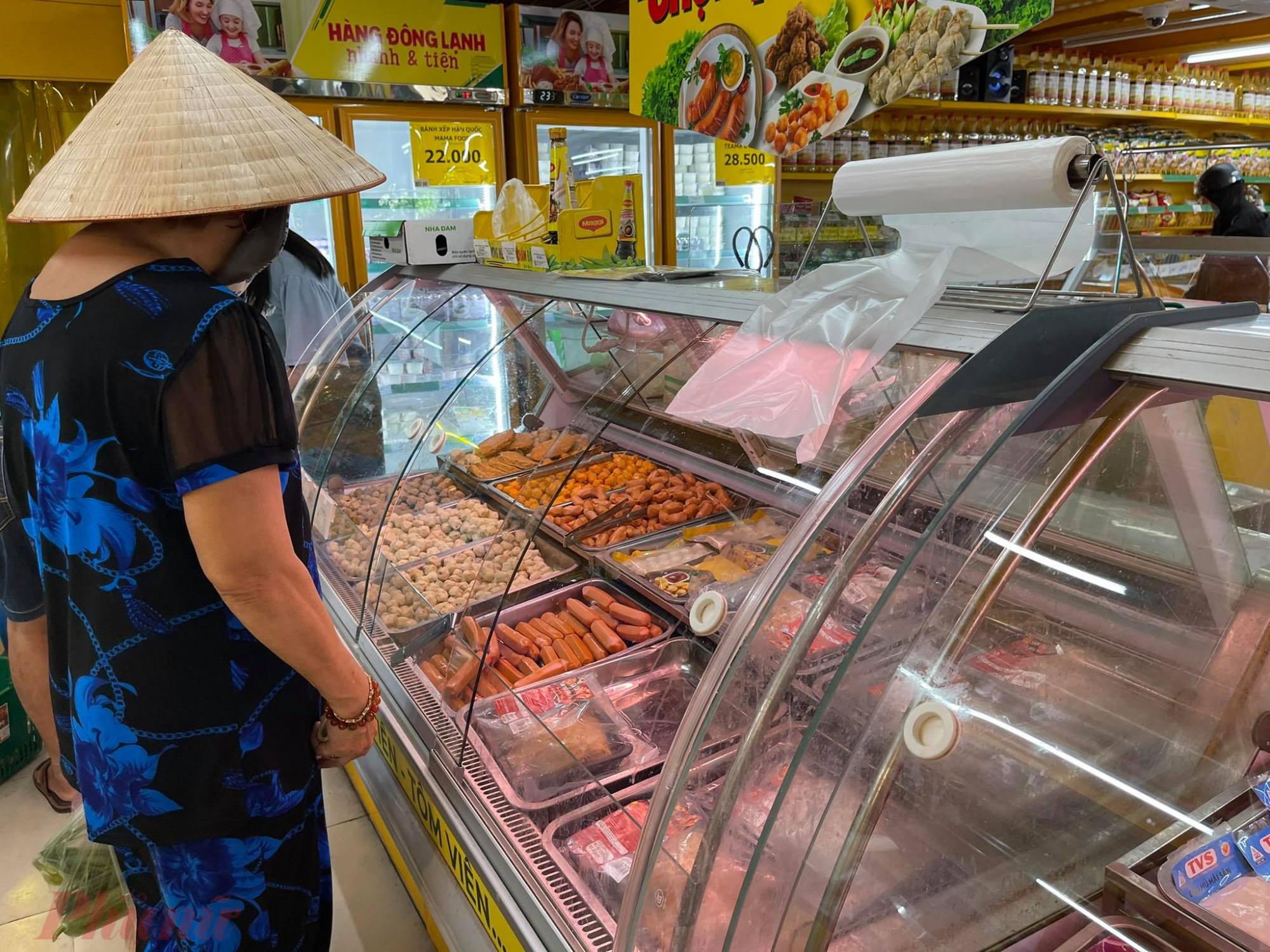 Tủ thịt hết hàng, nhân viên chêm thực phẩm đông lạnh cho khách mua thay thế.