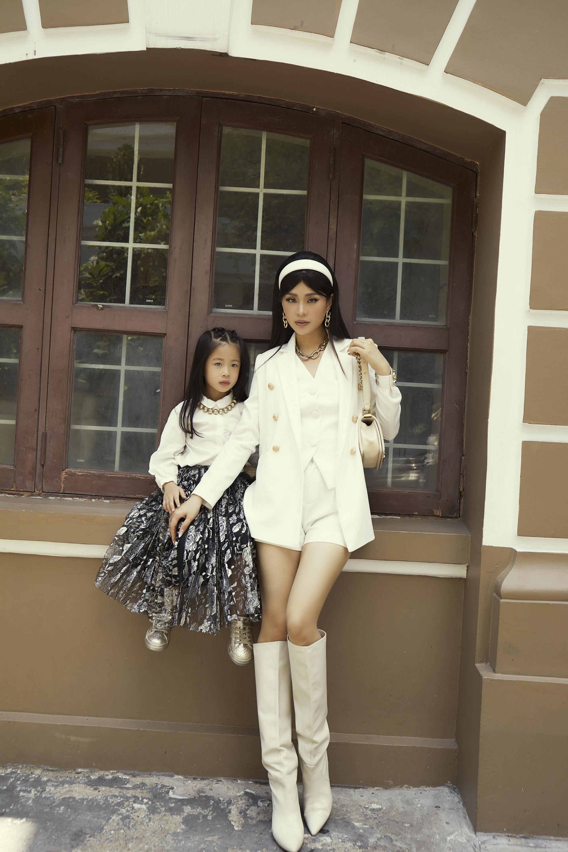 Diễm Trang diện trang phục với tông trắng làm chủ đạo. Bé Julia diện sơ mi trắng kết hợp với chân váy hoạ tiết trắng nền đen. Hai bộ trang phục đều được kết hợp với phụ kiện màu vàng kim to bản ấn tượng.