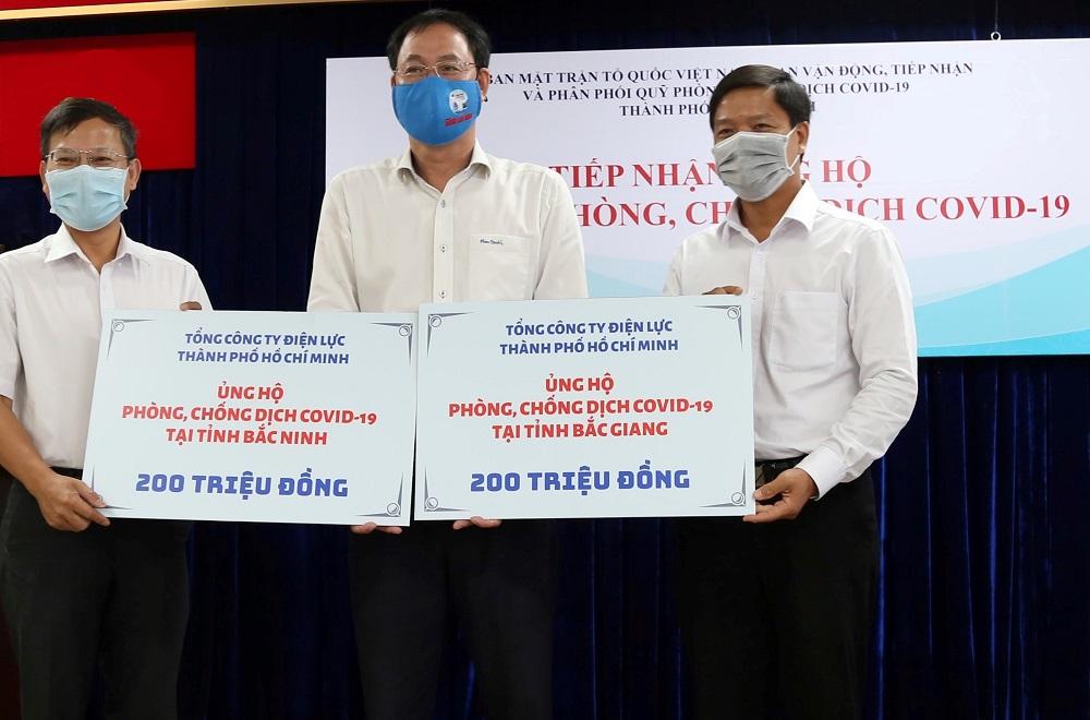 Ông Lê Văn Minh - Chủ tịch Công đoàn (phải) và ông Phạm Việt Anh - Phó trưởng Ban Truyền thông (trái) đại diện EVNHCMC trao 400 triệu đồng ủng hộ 2 tỉnh Bắc Giang, Bắc Ninh phòng, chống dịch COVID-19. Ảnh: Chi Lan