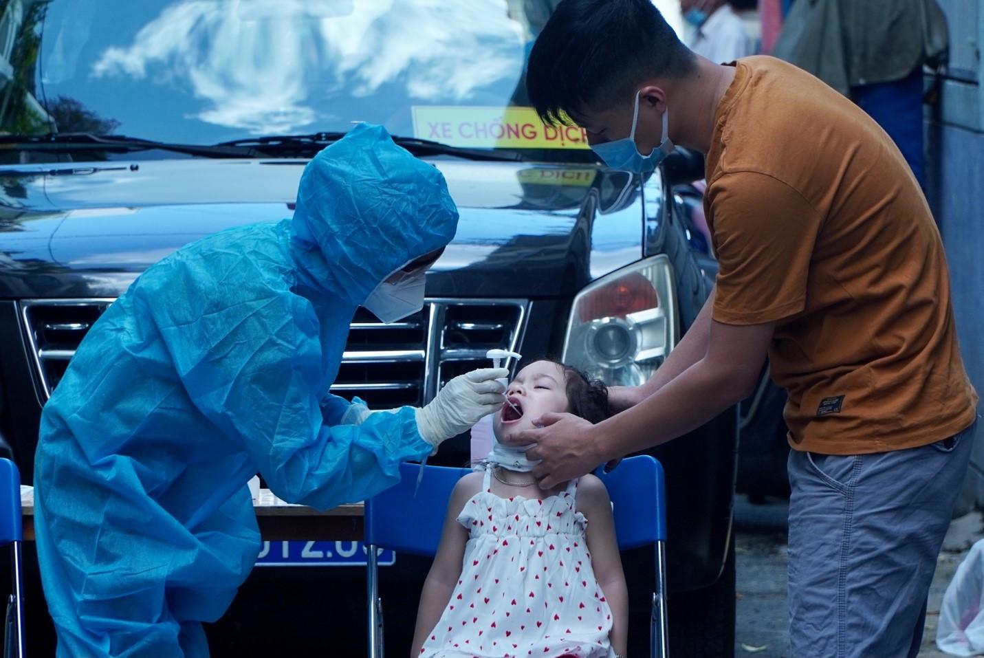 Lấy mẫu xét nghiệm cho một em bé ở quận 3 sau khi có 1 trường hợp nhiễm COVID-19 bị phát hiện. Ảnh: HCDC