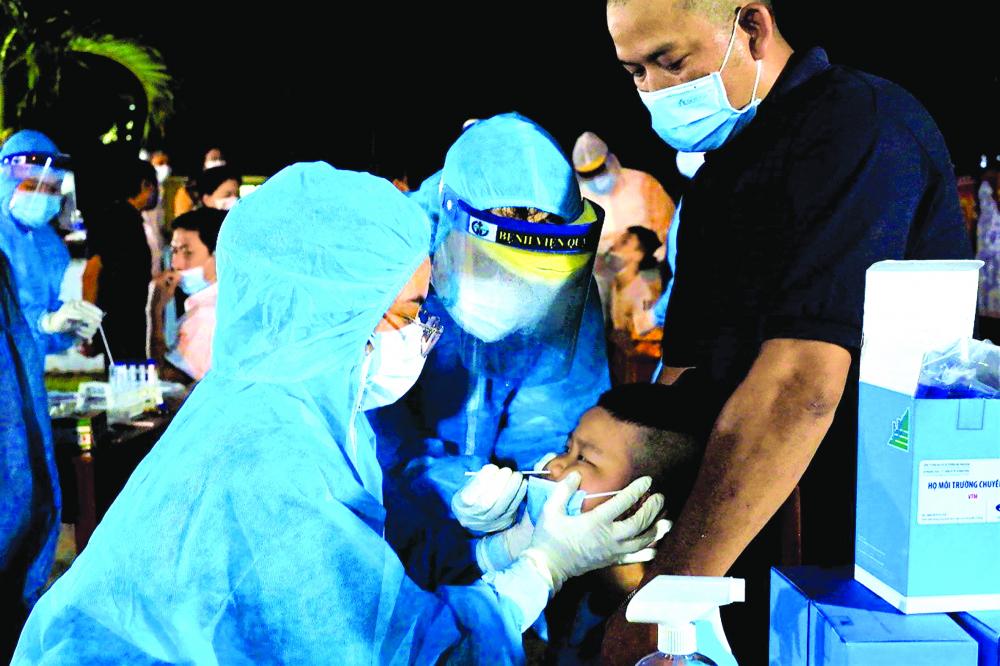 Lấy mẫu xét nghiệm COVID-19 cho một em bé ở P.9, Q.Gò Vấp, TP.HCM ẢNH: HCDC