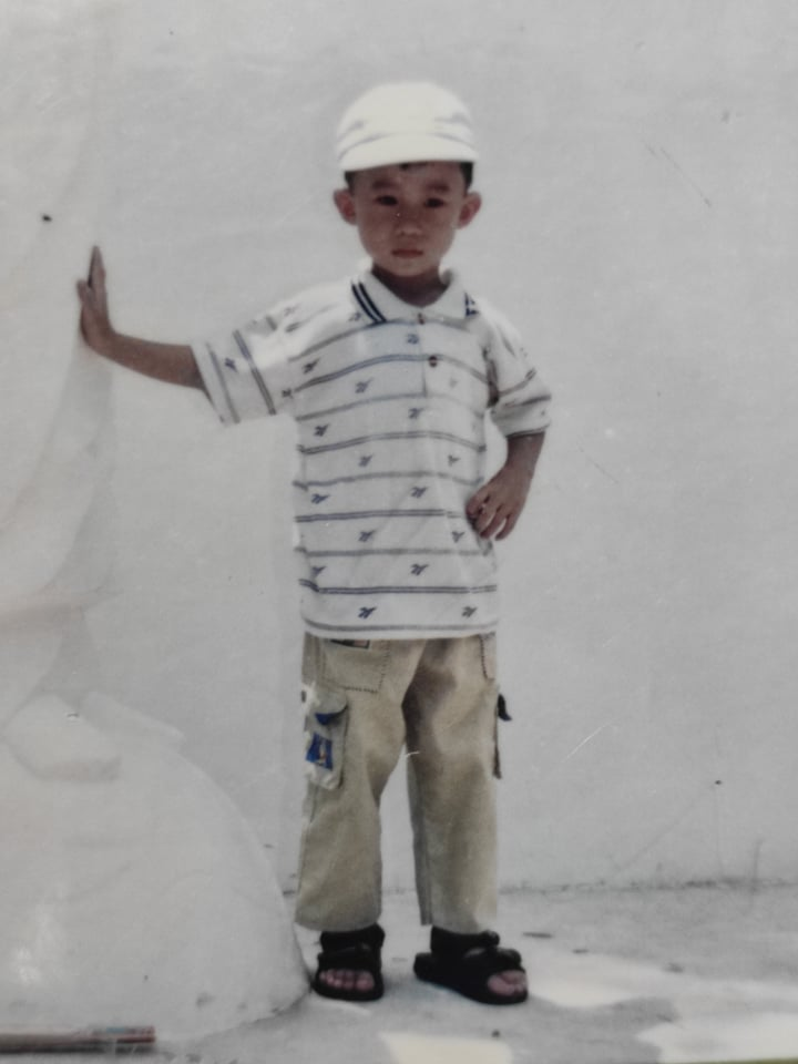Anh Trương Bá Tuấn (quê Kiên Giang) vẫn còn lưu giữ nhiều hình ảnh thuở bé. Tuấn cho biết bức ảnh này được chụp vào dịp rằm tháng 7 năm 1999. Lý giải về biểu cảm trong bức hình, Tuấn cho biết: Tôi nhớ lúc đó phải leo núi, đến đỉnh thì có tượng Phật nằm nên cha mẹ kêu chụp ảnh