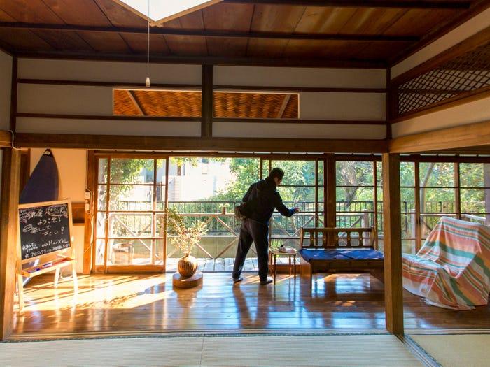 Một người quản lý bất động sản mở cửa sổ của một ngôi nhà truyền thống Nhật Bản bị bỏ trống ở thành phố Kamakura ngoại ô Tokyo