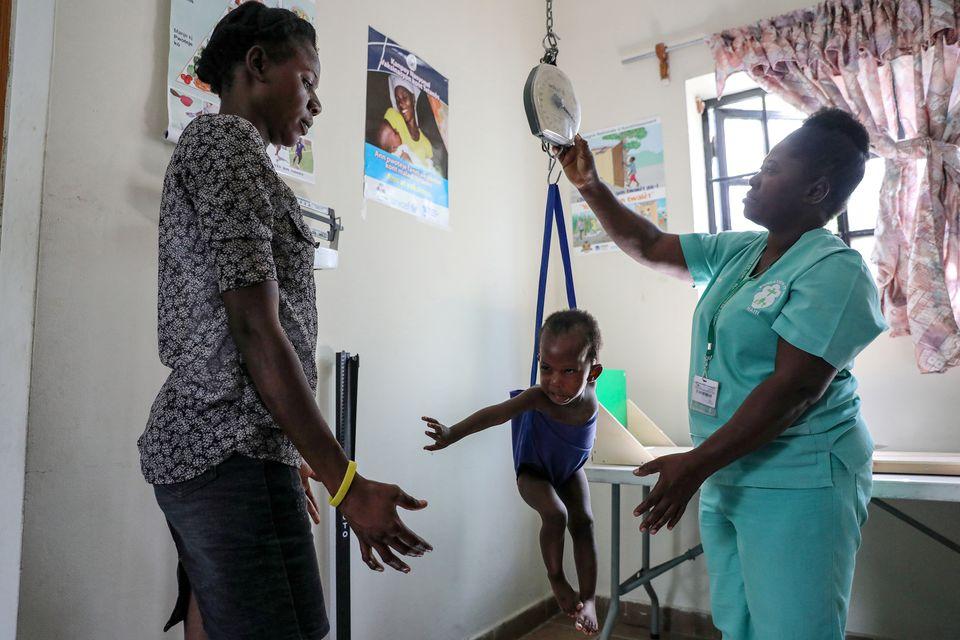 Một y tá cân một đứa trẻ trước mặt mẹ của nó tại Bệnh viện St. Luke ở Port-au-Prince, Haiti ngày 29 tháng 1 năm 2020. Ảnh chụp ngày 29 tháng 1 năm 2020. REUTERS / Valerie Baeriswyl / File Photo