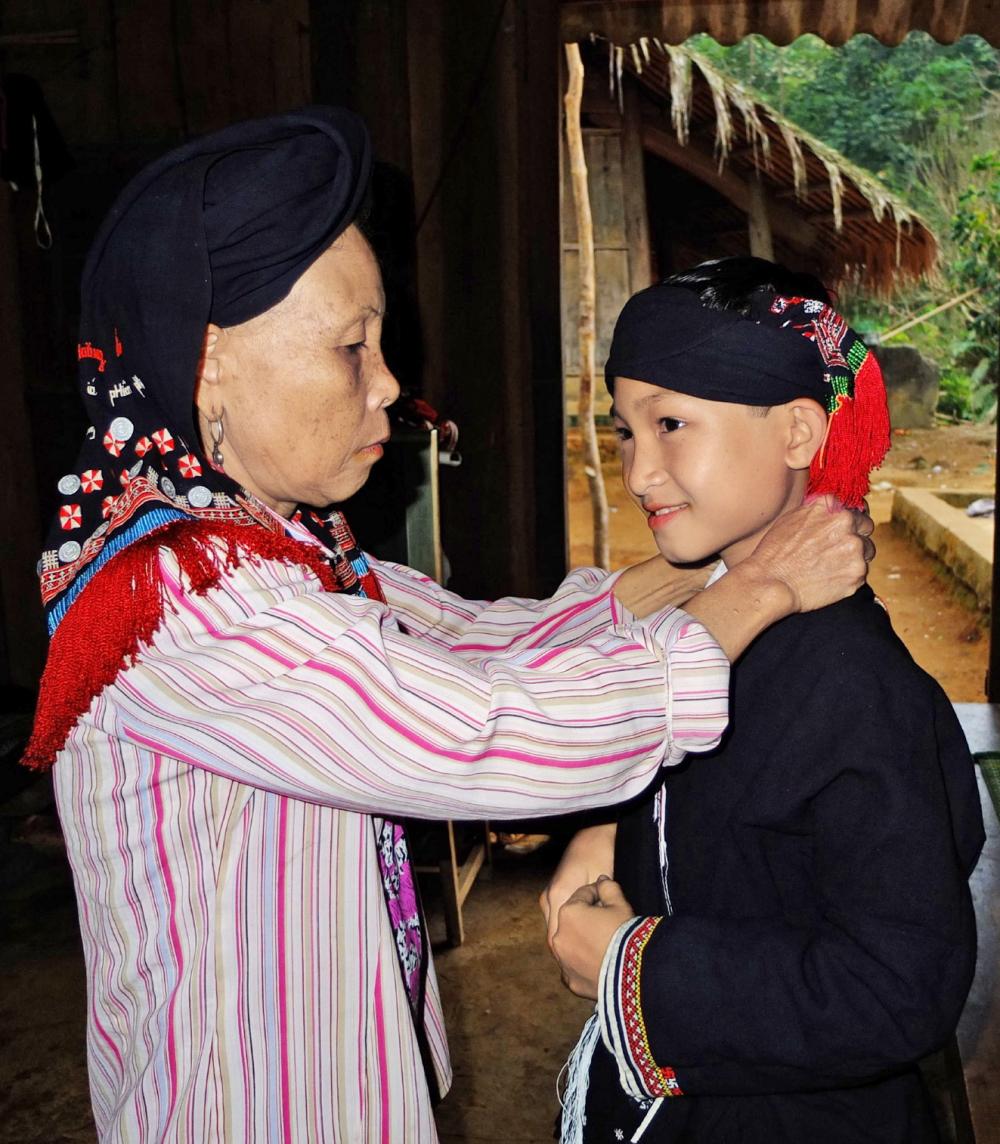 Bàn Văn Lý (phải) chuẩn bị trang phục để làm lễ lập tĩnh