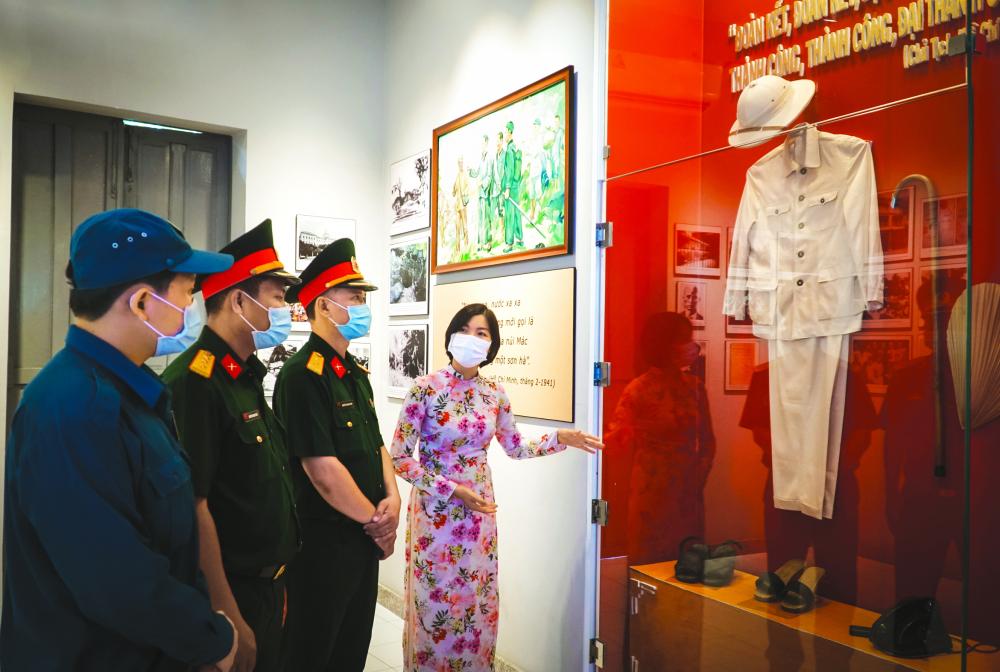 Chị Trần Thị Quyên thuyết minh cho du khách tham quan Nhà Bác Hồ ẢNH: TAM NGUYÊN