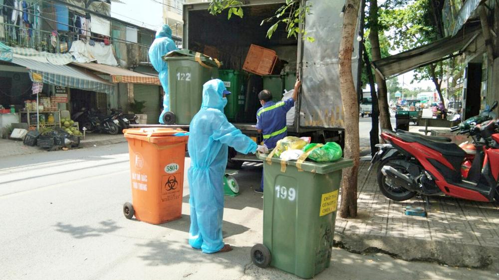Việc thu gom rác sinh hoạt trên địa bàn Q.Gò Vấp vẫn do các tổ lấy rác dân lập thực hiện với những bảo hộ rất đơn giản. Chỉ những khu vực bị phong tỏa mới có xe rác cùng nhân viên mặc bảo hộ phòng, chống dịch thu gom. Tuy nhiên, một người mặc đồ công nhân khác thì không mang bảo hộ mà chỉ mang một chiếc khẩu trang như thường nhật - Ảnh: Phan Tuyền