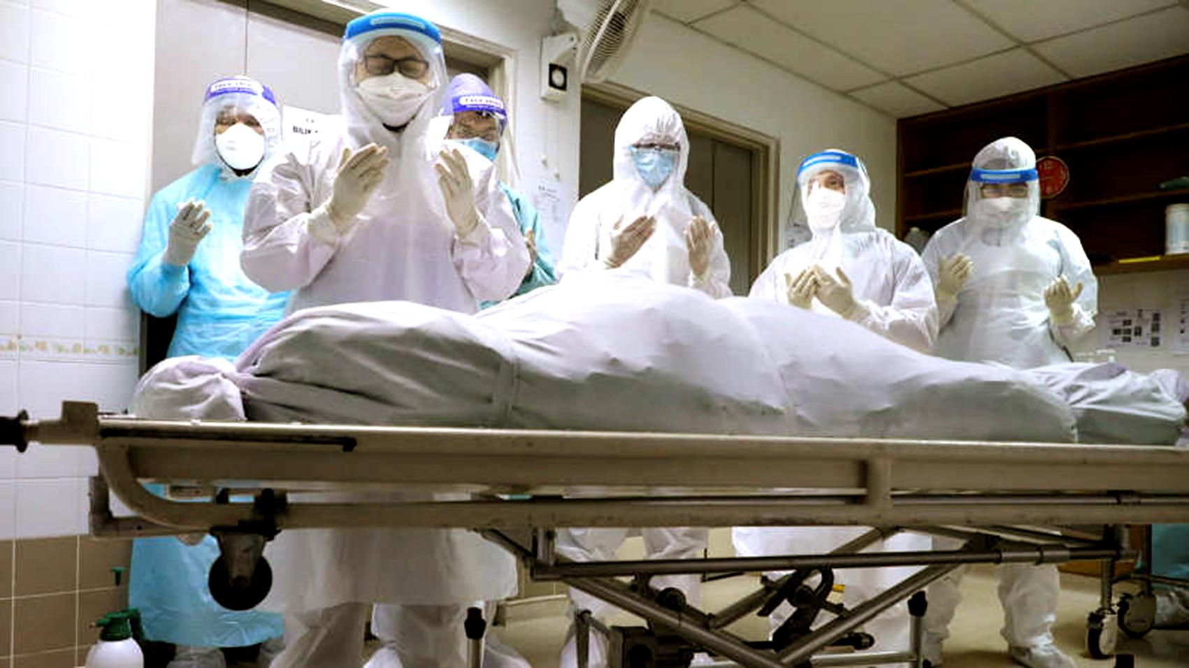 Người thân của một bệnh nhân chết vì COVID-19 cầu nguyện tại nhà xác bệnh viện ở Kuala Lumpur, Malaysia, vào cuối tháng Năm