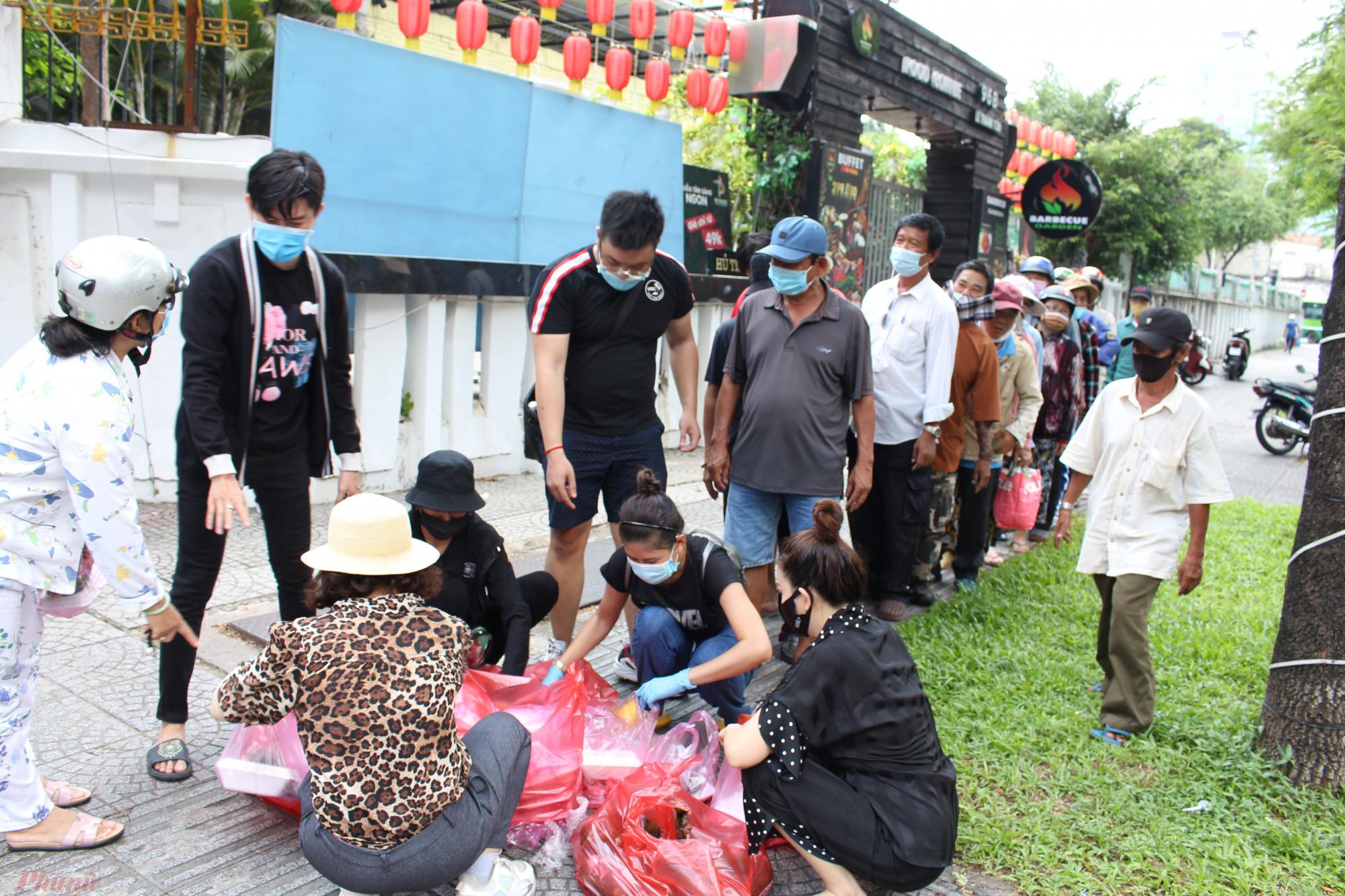 Người nghèo xếp hàng ngay ngắn, tuân thủ quy định phòng dịch bệnh COVID-19 trong lúc chờ phát cơm miễn phí trên đường Nguyễn Trung Trực, quận 1, TPHCM.