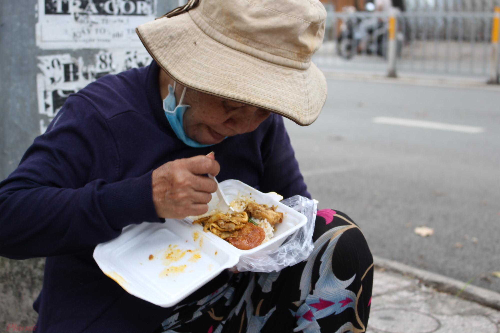Cụ bà bán vé số đói lả, nhận được hộp cơm từ cô Hòa, liền ngồi xuống bên đường ăn ngấu nghiến.