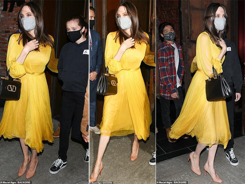 Angelina Jolie diện bộ đầm vàng, cùng các con vào một nhà hàng ăn tối.