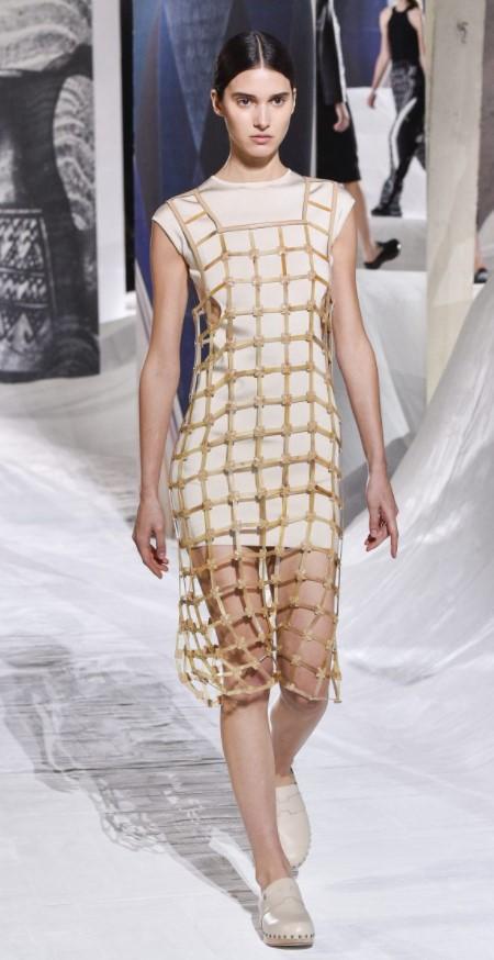 Hermes mang đến bộ trang phục trẻ trung với chiếc váy ngắn ôm dáng khoăc thêm thiết kế vải lưới bên ngoài vừa tạo điểm nhấn cho trang phục vừa thêm phần xu hướng. Lựa chọn màu vàng đồng phối cùng màu kem tạo nên tổng thể hòa hợp cho trang phục.