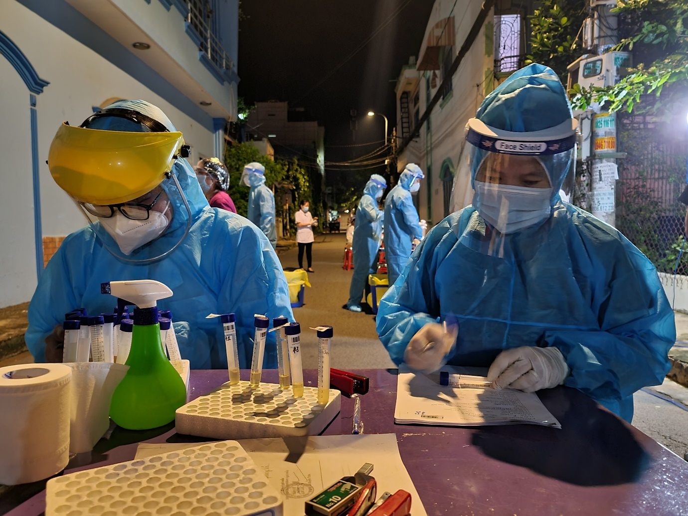 Nhân viên y tế lấy mẫu xét nghiệm trong khu vực phong tỏa khu dân cư Nam Long. Ảnh: HCDC