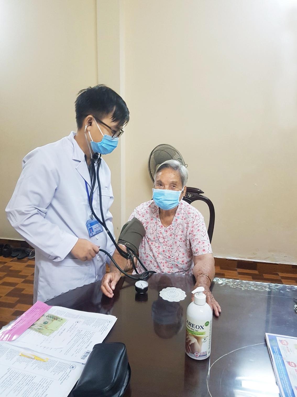 Bác sĩ Phạm Minh Công (Bệnh viện Thống Nhất) đang khám cho bệnh nhân cao tuổi nhiều bệnh lý nền tại nhà bệnh nhân tối 7/6