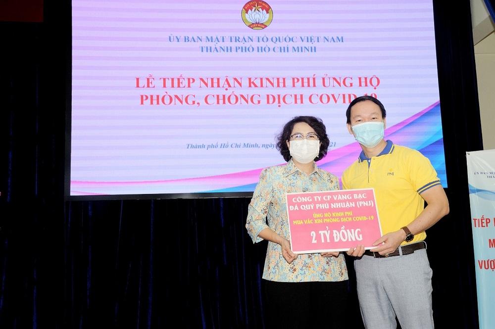 Ông Huỳnh Văn Tẩn, Giám đốc Truyền thông và Đối ngoại đại diện PNJ trao tặng 2 tỷ đồng kinh phí mua vắc-xin phòng, chống COVID-19 cho UBMTTQVN TPHCM. Ảnh: PNJ