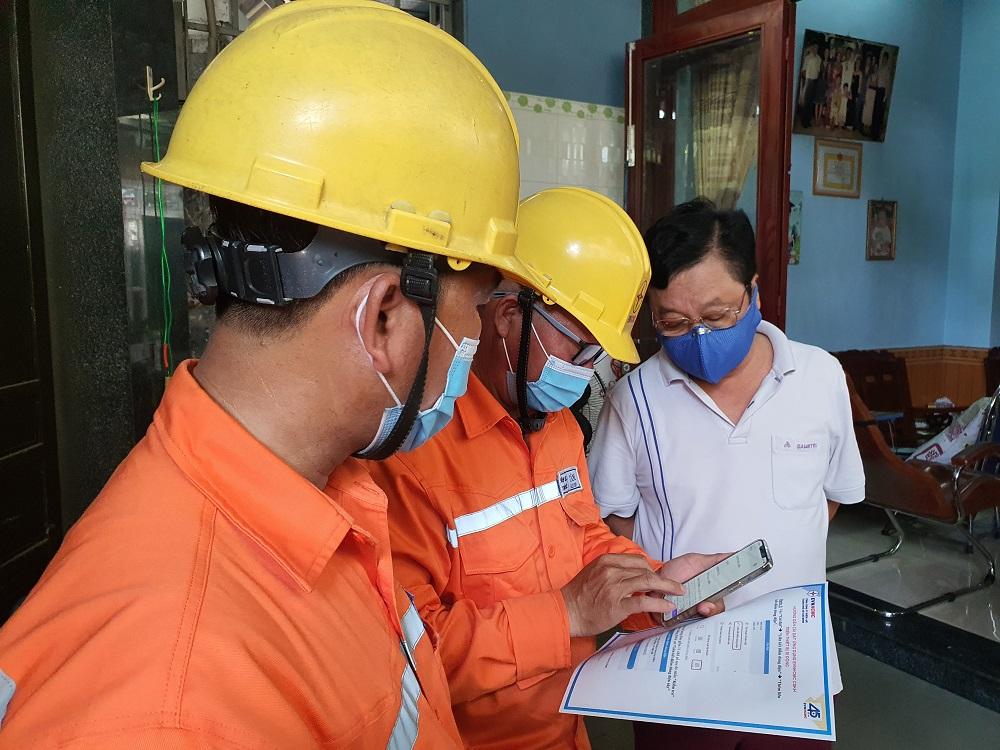 Nhân viên ngành điện hướng dẫn khách hàng cài đặt ứng dụng EVNHCMC CSKH trên thiết bị di động. Ảnh: EVNHCMC