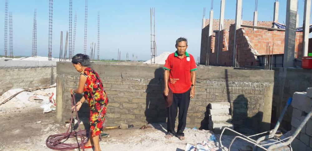 Vợ chồng ông Võ Ngọc Thành bên căn nhà mới đang xây tại khu tái định cư xen ghép Tân Bình